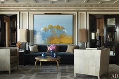The painting in the living room is by Charles Dix, and the vintage cocktail table and club chairs were designed by René Prou and Jean-Michel Frank, respectively.