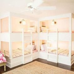 Sweet girls' bunk room features two pairs of bunk beds in L formation fitted with white ladders and dressed in pink polka dot bedding and pink stripe duvet covers illuminated by brass sconces with white plated shades. Corner Bunk Beds, Bunk Bed Rooms, Bunk Beds Built In, Cool Bunk Beds, Bunk Beds With Stairs, Kids Bunk Beds, Custom Bunk Beds, Modern Bunk Beds, Dream Homes