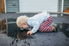 Stock photo of A toddler Boy Drinks Face down from a puddle on the asphalt by Amandavoelker Blue Rain, Face Down, Toddler Boys, Bean Bag Chair, Baby Boy, Blog, Little Boys, Beanbag Chair, Blogging