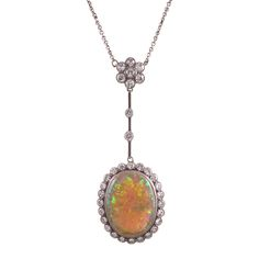 Edwardian Opal Diamond Gold Platinum Drop Necklace. Rendered in platinum over 18k yellow gold, with a 9.5 carat oval opal at the center of a frame of brilliant white diamonds. Each edge finished with milgrain. The design is both sophisticated and playful, with the major pendant swinging suspended from a diamond floret cluster. In total, the diamonds weigh approximately 2.5 carats. The necklace is offered in an original antique presentation box.