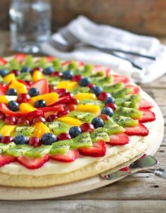This simple fruit pizza is beautiful and delicious! A soft sugar cookie crust with a cream cheese frosting and topped with sliced fruit. | pinchofyum.com
