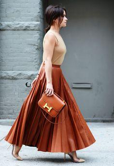 Cognac pleated leather skirt w/ matching clutch, nude cutout stilettos w/ matching sleeveless blouse, dark ponytail