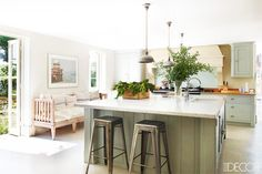 Kitchen with silver stools, white countertop, light floors, white walls, mint cabinets, and plants