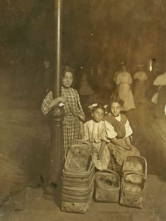 """Aug. 1908     Marie Costa, Basket Seller, 605 Elm St., Sixth St. Market, Cincinnati. 9 P.M. Had been there since 10 A.M. Sister and friend help her.     Caption information from """"The Library of Congress"""" on Flickr  Author: Edecio Martinez   Credit: Flickr/The Library of Congress"""