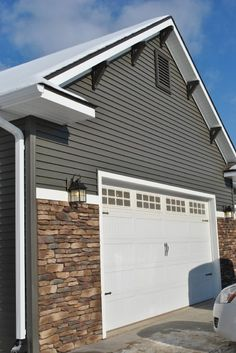Dark gray siding with stone accents, white trim. Michaud House - C&M Properties . Siding Colors For Houses, Exterior Siding Colors, House Paint Exterior, Exterior Design, Stone Exterior, Exterior Trim, Grey Siding House, Gray Siding, Stone Siding