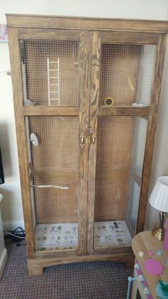DIY indoor aviary I made from an old wardrobe. Cut out some panels, added wire mesh, found and cleaned branches for perches, and added a lock in the front.