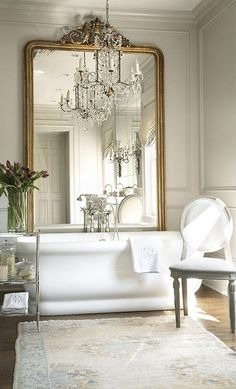 French master bath features gray walls accented with gray moldings alongside a gilt floor mirror leaning against a wall placed in front of a freestanding tub situated under a crystal chandelier paired alongside a polished nickel etagere and an oval back French chair alongside a blue and gray rug.