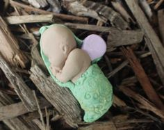 Decorate you garden or terrarium with this super cute miniature fairy baby! You can put your fairy baby outside or keep it inside (I keep mine on my nightstand!). I used clay and sparkles to create the fairy babies. This one measures 2 1/2 inches long. I have more wing colors available in my shop.  *Did you see the last picture of the baby sleeping in the crib? That cute wooden crib is made by Pixies Patch, also another shop on Etsy! So if you would like a cradle for your fairy baby head on…