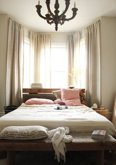 Low rustic wood platform bed placed in front of bay windows of a bedroom.