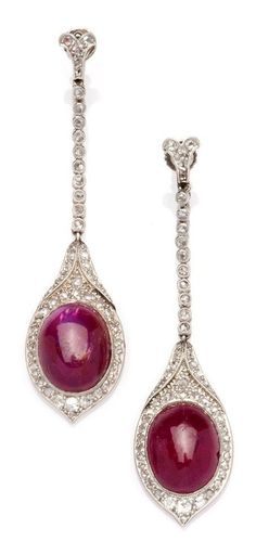 A pair of Art Deco ruby and diamond earrings, circa 1920. Each designed as a slender line of small diamonds terminating in two larger ruby cabochon drops surrounded by diamonds. #ArtDeco