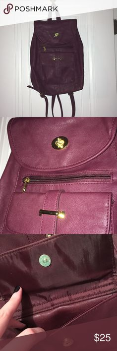 """Burgundy Mini backpack NWT Beautiful faux leather backpack in the color burgundy with gold zipper, etc. The last image is the closet to the color but looks slightly more purple in person. 2 pockets on the front (1 zipper and one magnetic clasp). The top portion opens by turning the gold piece. One zipper pocket on the inside and two additional pockets. There are also two buttons on the top that can be unbuttoned to expand the width of the bag on top.  Approximately 12"""" in height 9"""" in length…"""