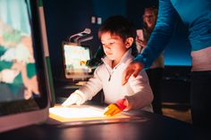 In the DinoLabs theater: A young visitor the Fort Worth Museum of Science and History scans a coloring page using an HP Sprout.
