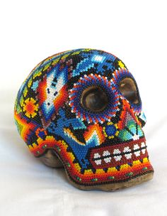 Huichol Skull. Handmade by Mexican artist Mario Carillo Avila.  Consists of pottery skull coated with beeswax and decorated with hundreds of hand-appied glass beads made in the Czech Republic. Buy Day of the Dead folk art online at Viva Oaxaca Folk Art.