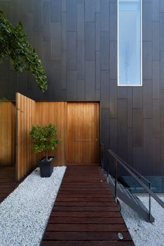 Cool grey house side paneling accented by the wood door, fence and walkway