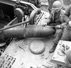 A American GI measures a projectile that would be fired by the Sturmtiger with R61 launcher system