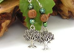Beautiful and symbolic handmade freshwater pearl earrings, with a stunning silver tone tree charm suspended from baroque deep green freshwater pearls and a dark brown wooden bead. Think organic, natural, the tree of life, the colours of nature and the. Blue Forest, Earring Tree, Wooden Beads, Sterling Silver Earrings, Charmed, Drop Earrings, Pearls, Handmade, Gifts