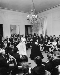 1951 - Christian Dior fashion show - Two French models showing off evening dresses while surrounded by eager crowd of buyers.