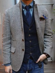 Pair a grey herringbone wool blazer with blue jeans to create a smart casual look.  Shop this look for $190:  http://lookastic.com/men/looks/denim-shirt-and-tie-and-pocket-square-and-waistcoat-and-blazer-and-jeans/4008  — Blue Denim Shirt  — Navy Knit Tie  — Brown Paisley Pocket Square  — Navy Corduroy Waistcoat  — Grey Herringbone Wool Blazer  — Blue Jeans