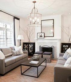 salon très charmant, canapé gris magnifique, cheminée et peinture murale blanche, lustre design extraordinaire, amenagement salon exquis