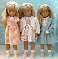 Checked pinafore with t shirt; smocked dress with cardigan and a pretty blouse with blue skirt worn with blue patterned cardigan all wearing shoes by Alcraft Creations