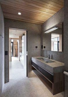 parement mural en béton, lavabo design assorti et faux plafond bois assorti