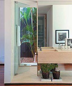 O arquiteto Guilherme Torres garantiu luz natural aos ambientes. Painéis de vidro trazem a claridade do jardim para o banheiro. Uma porta do mesmo material preserva a área do banho.