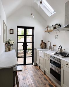 Galley kitchen extension with black aluminium doors, restored floor boards, marble work surface, belfast sink and velux window. White Galley Kitchens, Galley Kitchen Design, Galley Kitchen Remodel, Ikea Galley Kitchen, Kitchens Uk, Soapstone Kitchen, Kitchen Shelves, Kitchen Designs, Kitchen Countertops