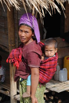 A woman with baby in a baby wrap/papoose, Mae Yay Village, Myanmar. We'll be opening a new school soon so this is also a photo of a future pupil! We're #UpForSchool in Myanmar. Mae Yay Village will be the fourth UWS school in Myanmar.