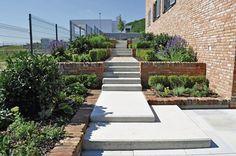 Na južnej strane pozemku sú vysadené najmä liečivé rastliny, dlho kvitnúce trvalky, vždyzelené vavrínovce a krušpány. Priama línia chodníka so schodmi z liateho betónu príjemne kontrastuje s rustikálnou fasádou a múrikmi.