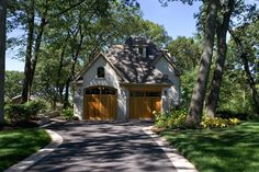 Plain asphalt driveway is given character and interest with a cobblestone border.  Also, don't you just love these garage doors!