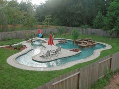 Garden and Patio, Small Backyard Lazy River Pool With Lounge Area In The Middle Plus Stone Waterfall Surrounded By Green Grass And Wooden Fence Ideas ~ Backyard Lazy River