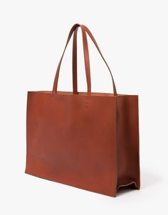 From Cuero&Mør, a minimalist smooth leather large tote in Cognac.  Features two shoulder straps, unlined, front gold pressed logo, rectangular silhouette and standing structure.  •Smooth leather bag in Cognac •Two shoulder straps •Unlined •Front