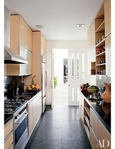 Interior designer Richard Mishaan's home in Cartagena, Colombia, has a galley-style kitchen with oak cabinetry, black granite countertops, and a slate floor; the French doors open onto the courtyard.