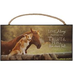 A sentimental and inspirational design, this pressed wood hanging sign features a portrait of a dog sitting next to a horse with the words love always protects, trusts, hopes. Love never fails. I Cor.