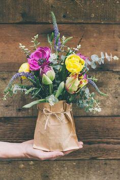 Ein Blumen Arrangement im Frühling mit Brotpapier als Geschenk verpacken