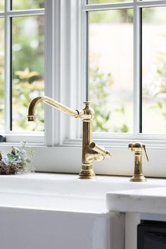 An antique brass vintage faucet is paired with a farmhouse sink and fixed in fro. An antique brass vintage faucet is paired with a farmhouse sink and fixed in fro. An antique brass vintage faucet is p. White Kitchen Faucet, Farmhouse Sink Kitchen, Farm Sink, Kitchen Hardware, Modern Farmhouse, Kitchen Faucets, Kitchen Fixtures, Bathroom Faucets, Farmhouse Style