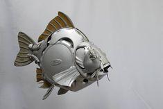 Escultura con forma de pez hecha a base de reciclaje de tapacubos y llantas de coche