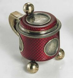 A SILVER-GILT AND GUILLOCHÉ ENAMEL MINIATURE TANKARD   MARKED K. FABERGÉ WITH THE IMPERIAL WARRANT, WITH THE WORKMASTER'S MARK OF ANDERS (ANTTI) NEVALAINEN, 1899-1904, SCRATCHED INVENTORY NUMBER 5570  Cylindrical on three ball feet, the body enameled in translucent red over a basketweave guilloché ground, the front, sides and hinged cover inset with coins depicting Empress Catherine II, with ball thumb-piece and angular handle, with gilt interior, marked under base