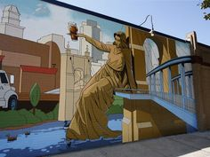 "New mural toasts Sam Adams, Cincy brewing. Photo: Tyler Davidson's ""Genuis of Water"" is perched on the Roebling Bridge while raising her glass. The Enquirer/Kareem Elgazzar"