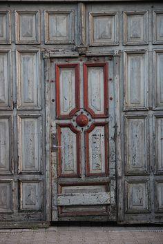 Uma antiga porta em uma parede toda de madeira. Fotografia: Benny Traeger Hünersen no Flickr.