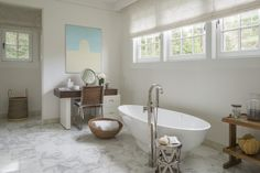 A tub by Agape is the centerpiece of the master bath, where a vanity mirror by Exhibit Modern is paired with a desk by Lawson Fenning and a McGuire chair. The tub filler is by Graff, and the stool is from One Kings Lane.