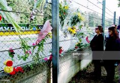Fans of the late Brazilian Formula One triple world champion Ayrton Senna stand 02 May 1994 near the wall where Senna crashed at the wheel of his Williams-Renault 01 May during the San Marino F1 Grand Prix. Senna died at a Bologna hospital shortly after the accident.
