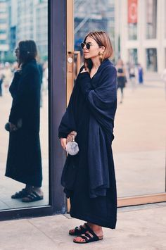 Blogger Maja Wyh wears gold earrings with round sunglasses, an oversized wrap, a long skirt and Birkenstock sandals.