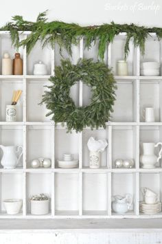Vintage wooden cubby shelf with fresh Christmas greenery. Ironstone and ornaments. Vintage, country farmhouse style. Farmhouse Christmas. Buckets of Burlap