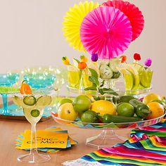 Make a magnifico margarita station by displaying garnishes in shot glasses on stacked cake stands. Click for more muy bien Cinco de Mayo party ideas!