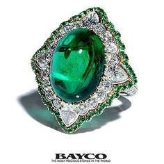 A platinum and gold ring centered upon a 12 carat oval cabochon Zambian emerald set within a round and pear-shaped diamond cluster which is in turn set within an emerald micropavé surround.