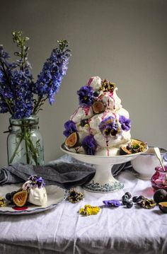 earl grey pistachio meringue tower with blueberries and figs and edible flowers