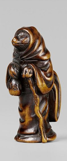A boxwood netsuke of the fox or tanuki dressed as a woman. First half 19th century