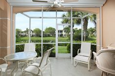 Spacious covered screened-in lanai with dining area and ceiling fan.