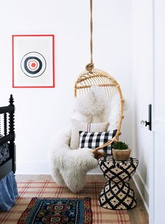 Seating nook with suspended hanging chair, sheepskin, and geo rattan side table.